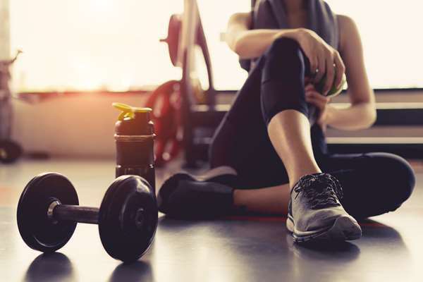 Jak szybko schudnąć bez diety? Kobieta odpoczywa po ćwiczeniach na siłowni